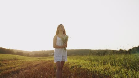 rüya gibi : Pretty girl in white dress standing in field with bouquet of flowers, looking at clear evening sky Stok Video