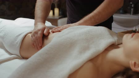 celulitida : Young woman receiving stomach massage at spa salon, relaxing lying on massage table during rejuvenation procedure. Masseur hands moves slow burning fat by anti-cellulite massage