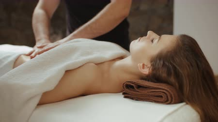 az yağlı : Woman receiving stomach massage at spa salon. Relaxing lying on massage table during rejuvenation procedure, male masseur hands burn fat by anti-cellulite massage