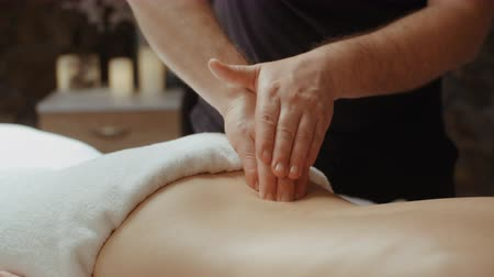scoliosis : Male masseur doing back massage. Slim woman receiving lumbar massage in spa, relaxing lying on massage table