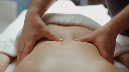 gyógyász : Male masseur doing back lumbar massage. Slim woman receiving health procedure in spa salon, relaxing lying on massage table