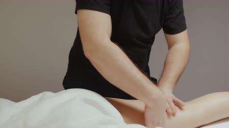 baixo teor de gordura : Male masseur doing leg hip anti cellulite massage. Slim young woman receiving health body rejuvenating procedure in spa salon