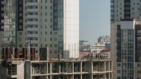constructing : Constructors working at construction site residential estate building in city. Workers moving fast work with steel rebar and concrete welder working sunny day zoom out time lapse shot