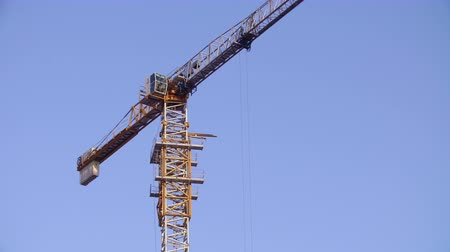 гражданский : Tower crane working on construction site sunny day clear blue sky on background sunny day