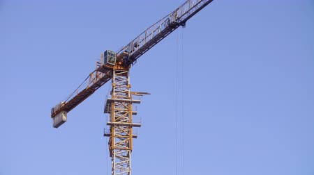 гражданский : Tower crane working on construction site sunny day clear blue sky on background Стоковые видеозаписи