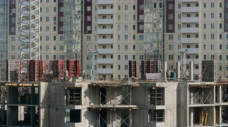 constructing : Constructors working at construction site residential building in city. Workers work with steel rebar structures sunny day time lapse shot