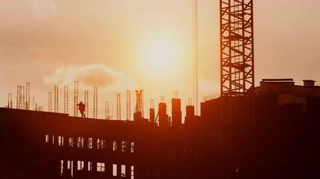 Tower crane working on construction site elevate steel structures weight, constructors working on residential building sunny evening, golden hour