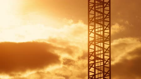 The ladder of tower crane on construction site in sunset light, warm orange sky with moving clouds on background, morning or evening golden hour Stock Footage