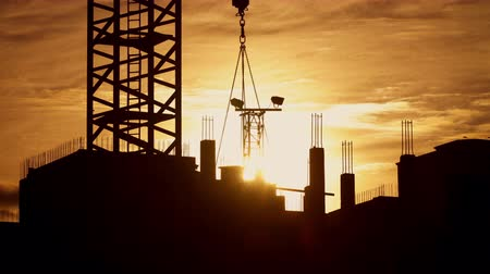 construtor : Silhouette of tower crane working on construction site elevate concrete mixer, constructors working on residential building sunny evening, golden hour, warm cloudy sky
