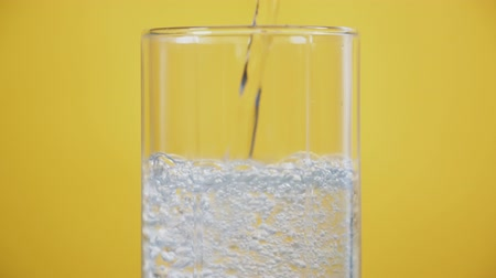 aerated : Pouring soda with gas bubbles in glass on a yellow background at summer party, refreshing drink clean sparkling water pours in slow motion