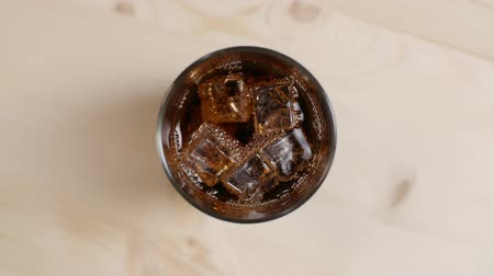 Top view glass full of cola fizzy drink with ice cubes on light brown wooden table, close up of cold sparkling soda on beige background, slow motion Stock Footage