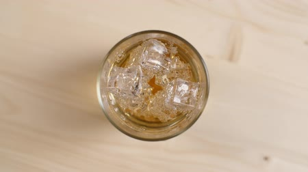 Top view glass full of cream soda drink with ice cubes on light brown wooden table, close up of cold fizzy sparkling soda on beige background, slow motion Stock Footage
