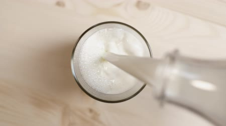 cálcio : Top view of milk being poured in a glass on light brown wooden table, close up of milk pouring from transparent bottle on beige background, slow motion Vídeos