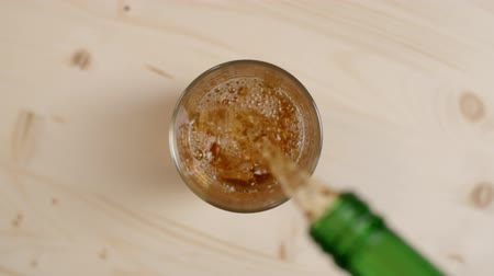bourbon whisky : Top view of alcoholic beverage being poured in a glass with ice cubes on light brown wooden table, cold rum or whiskey drink pouring from green bottle on beige background, slow motion