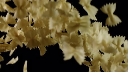 Yellow farfalle pasta bouncing and falling down on black background. Pile of raw macaroni flies after being exploded shot in slow motion