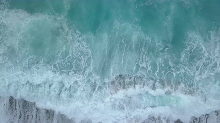 Aerial top view of sea waves foaming and splashing, big waves from above rolling and breaking on empty ocean beach. Zoom out drone shot Stock Footage