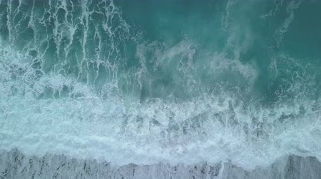 alcançando : Aerial top view turquoise waves break on empty sand beach. Clean sea waves from birds eye view, ocean waves reaching shore splashing and breaking, storm on sea from above