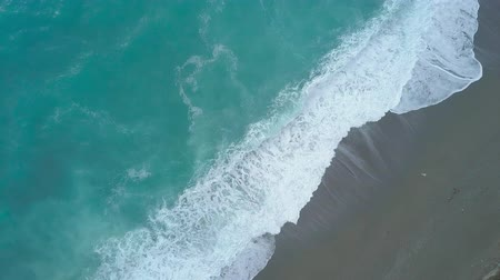 Aerial top view of turquoise sea waves foaming and splashing, big waves reaching shore from above rolling and breaking on empty ocean beach