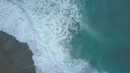 Aerial top view of stormy turquoise sea waves foaming and splashing, big waves from above rolling and breaking on empty ocean beach