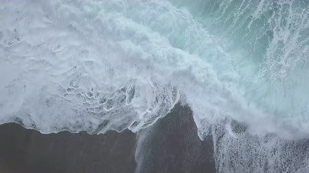 Aerial top view of sea waves foaming and splashing, big waves from above rolling and breaking on empty ocean beach. Zoom in drone shot Stock Footage