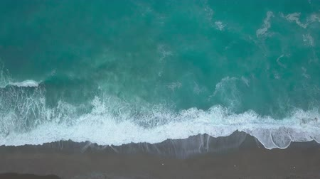 Aerial top view turquoise sea waves break on empty sand beach. Clean sea waves from birds eye view, ocean waves reaching shore and splashing from above Stock Footage