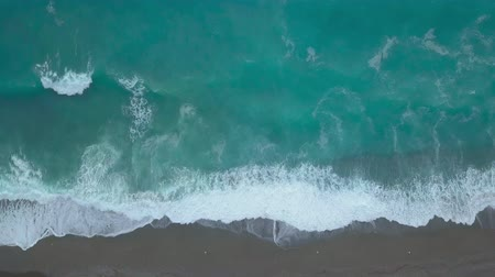 Aerial top view of turquoise sea waves foaming and splashing, big waves from above rolling and breaking on empty ocean beach