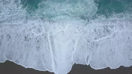 Aerial top view turquoise waves break on empty sand beach. Clean sea waves from birds eye view, ocean waves reaching shore splashing and breaking, storm on sea from above