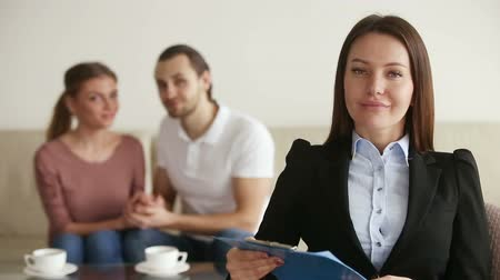 reconcile : Portrait of professional female relationship therapist sitting in her office after therapy session looking at camera with confident friendly expression, young reconciled couple on the background Stock Footage