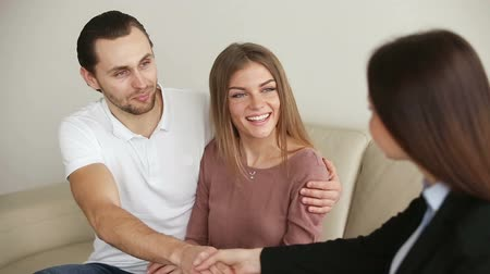 biztosítás : Young attractive happy smiling casual couple meeting consultant in the office or at home. Cheerful man embracing his wife and shaking hands with female expert after reaching agreement in agency Stock mozgókép