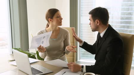 Irritated young businessman and businesswoman arguing at workplace, client holding, pointing at paper, having dispute about work issues, finding discrepancy in paperwork, blaming each other for error