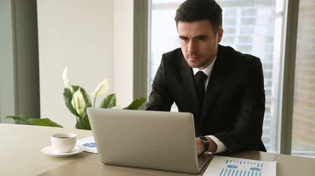 small businessman : Confident cheerful businessman in suit using laptop sitting at workplace, working on project, then looking at camera and smiling. Successful young entrepreneur at work, business owner at own office