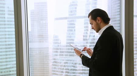 phablet : Confident happy businessman wearing suit standing near big window in office, holding tablet or smartphone, enjoying urban view, texting messages, using mobile apps for business, responding e-mails