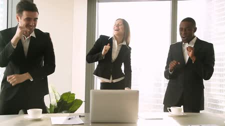 projects : Three cheerful businesspeople dancing at workplace desk, staff party, celebrating victory, successful deal, satisfied with teamwork result, excited by good news, yes we did it, won profitable contract