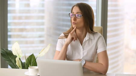 тренировка : Smiling young confident businesswoman in glasses looking at camera, sitting at office desk, talking. Call, promotion, video blogging, online webinar training, educational vlog, how to start business Стоковые видеозаписи
