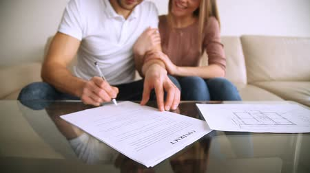 primeiro plano : Happy married couple signing contract of sale purchase, hugging, satisfied young clients putting signature on mortgage loan agreement, buying renting real estate, making property investment. Close up
