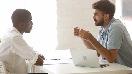 de brainstorming : Two diverse african and caucasian businessmen talking sitting at office desk, brainstorming discussing teamwork at workplace, serious partners having negotiations dialogue about problem in business Vídeos