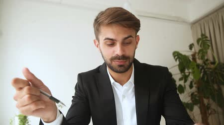 партнеры : Young successful businessman talking by video call, serious man negotiating with partner by web camera, making offer to investor using app for discussing business documents distantly remotely online
