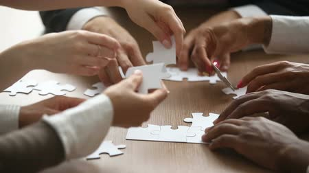 praca zespołowa : Close up view of business people hands trying to connect assembling jigsaw puzzle and join pieces on conference table in office, team help and support, finding right solutions in teamwork concept
