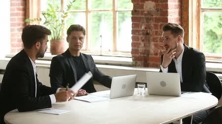 solicitor : Businessman holding documents with infographic statistics, presenting new project to investors, convincing clients to make deal, negotiating with partners on meeting at conference table with laptops Stock Footage