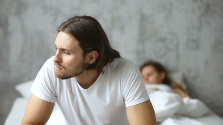 кризис : Thoughtful worried man sitting on the side of bed with sleeping woman at background, doubtful upset husband thinking of breaking up divorce, feeling unsure frustrated obsessed about family problem