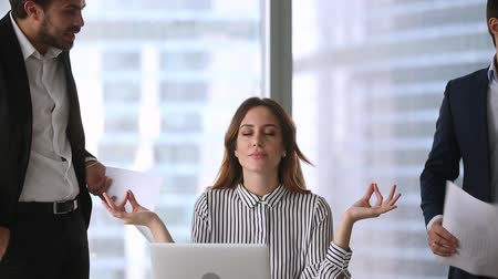 önlemek : Calm businesswoman professional taking break meditating at work ignoring angry colleagues disturbing clients, mindful healthy female boss doing yoga feeling no stress zen balance at office workplace Stok Video