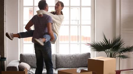 kendi : Happy couple renters owners tenants celebrate moving day in own flat, excited man husband holding carrying woman wife having fun among cardboard boxes package enjoy relocation into new home apartment Stok Video