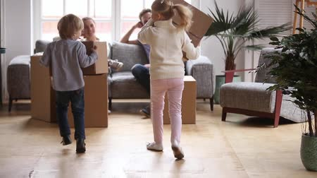 domy : Happy cute little children playing in living room enjoying moving day with parents, excited kids running carrying boxes having fun together unpacking in new modern home flat, family mortgage concept Dostupné videozáznamy