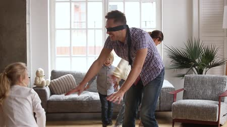 domy : Cheerful family with blindfolded father playing hide and clap game, happy parents and children having fun laughing in living room, cute kids escaping from dad catching spending time together at home Dostupné videozáznamy