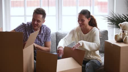coisas : Happy young couple laughing talking unpacking open cardboard boxes together after relocation, tenants renters sitting on sofa settle in unbox belongings moving in new home apartment concept