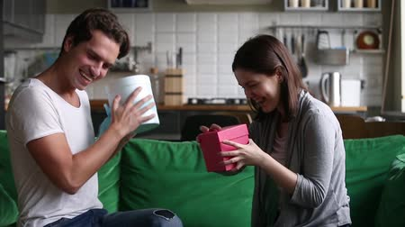 plezant : Excited happy young teen couple exchanging gifts on holiday sitting on sofa at home, happy millennial man and woman having fun giving opening boxes with romantic presents celebrating Valentines day Stockvideo