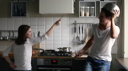 panelas : Funny young couple pretending fight battle kitchen war holding utensils having fun cooking together, happy playful man and woman laughing enjoying preparing food struggling with kitchenware at home Stock Footage