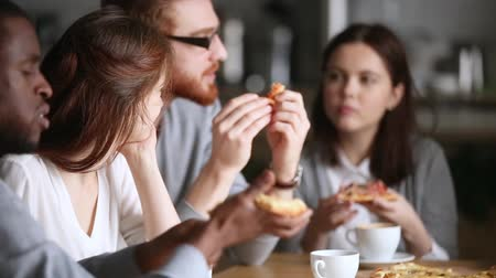 mates : Happy diverse millennial people mates group talking eating pizza in pizzeria sharing meal sitting at cafe table, multi ethnic friends team hangout together having fun conversation chatting at meeting Stock Footage