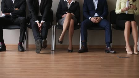 vaga : Jobless business people applicants group sitting in chairs in queue line row waiting for their turn company job interview, human resources, recruiting and employment concept, staff legs close up view