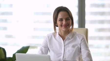 kifinomult : Smiling female successful millennial businesswoman looking at camera posing in office at workplace with laptop, happy confident friendly lady professional administrator secretary executive portrait